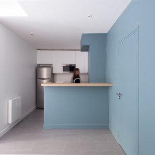 Ejemplo de comedor contemporáneo, grande, abierto, sin chimenea, con paredes blancas, suelo de cemento, marco de chimenea de hormigón y suelo gris