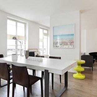 Réalisation d'une salle à manger ouverte sur le salon design avec un mur blanc et un sol en bois clair.