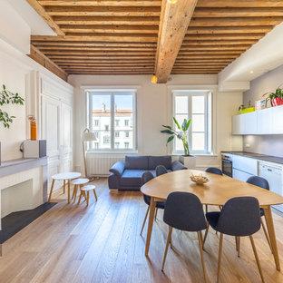 Exemple d'une salle à manger ouverte sur le salon scandinave de taille moyenne avec un mur blanc, un sol en contreplaqué, une cheminée standard, un manteau de cheminée en pierre et un sol beige.