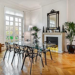 Inspiration pour une salle à manger ouverte sur le salon traditionnelle avec un mur blanc, une cheminée standard, un manteau de cheminée en pierre et un sol en bois brun.