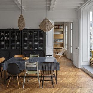 Aménagement d'une salle à manger classique fermée avec un mur blanc, un sol en bois brun et un sol marron.