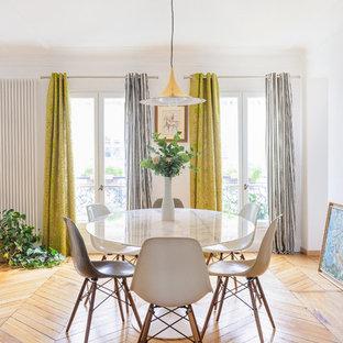 Cette photo montre une salle à manger tendance avec un mur blanc et un sol en bois brun.
