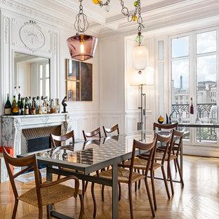 Idée de décoration pour une grand salle à manger ouverte sur le salon tradition avec un mur blanc, un sol en bois clair, un manteau de cheminée en pierre et une cheminée standard.
