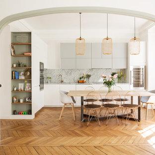 Réalisation d'une salle à manger ouverte sur le salon nordique de taille moyenne avec un mur blanc, aucune cheminée, un sol marron et un sol en bois brun.
