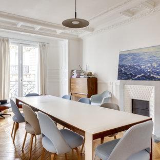 Aménagement d'une salle à manger scandinave avec un mur blanc, un sol en bois brun et une cheminée standard.