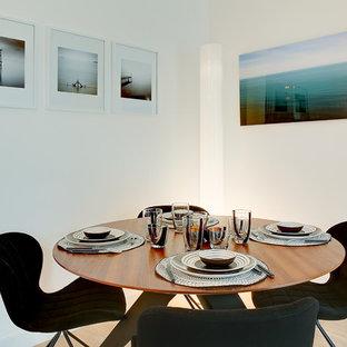 Idée de décoration pour une salle à manger design fermée avec un mur blanc et un sol en bois clair.