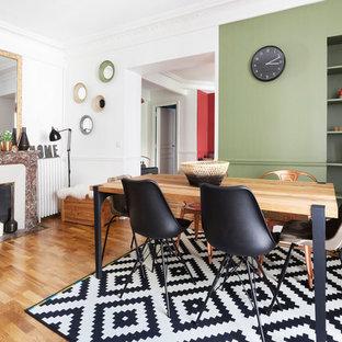 Foto de comedor actual, de tamaño medio, cerrado, con paredes verdes, suelo de madera clara y chimenea tradicional