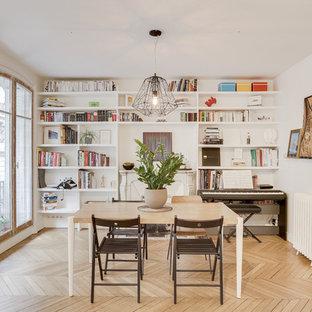 Inspiration pour une salle à manger nordique de taille moyenne et fermée avec un mur blanc, un sol en bois clair, une cheminée standard, un manteau de cheminée en pierre et un sol beige.