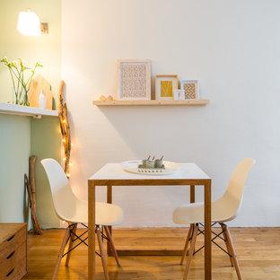 Exemple d'une salle à manger ouverte sur la cuisine scandinave de taille moyenne avec un mur blanc et un sol en bois brun.