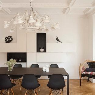 Exemple d'une salle à manger tendance fermée avec un mur blanc et un sol en bois clair.