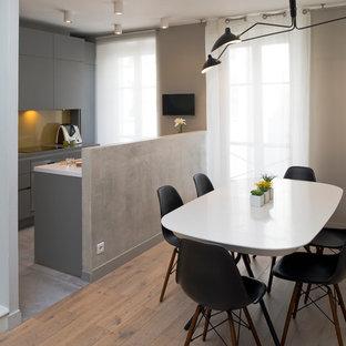 Cette image montre une salle à manger ouverte sur la cuisine design avec un mur gris et un sol marron.