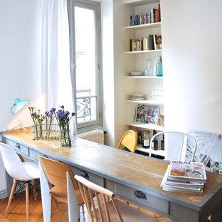 Aménagement d'une salle à manger éclectique avec un mur blanc et un sol en bois brun.