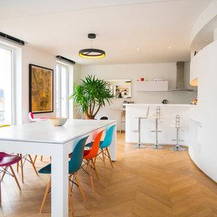 Inspiration pour une salle à manger ouverte sur la cuisine design avec un mur blanc, un sol en bois brun et aucune cheminée.