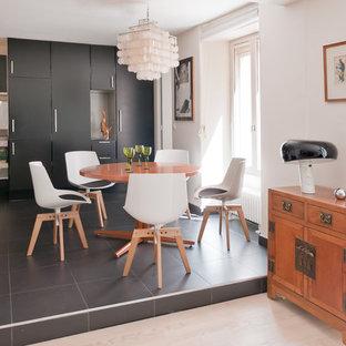 Cette image montre une salle à manger ouverte sur la cuisine design de taille moyenne avec un mur blanc et un sol en carrelage de céramique.