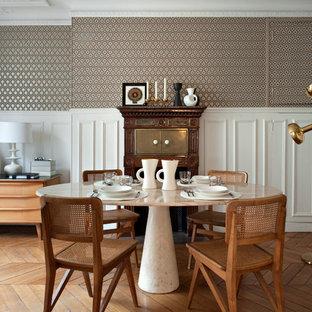 Aménagement d'une salle à manger classique fermée et de taille moyenne avec un mur multicolore et un sol en bois brun.