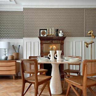 This is an example of a mid-sized transitional dining room in Paris with multi-coloured walls and medium hardwood floors.