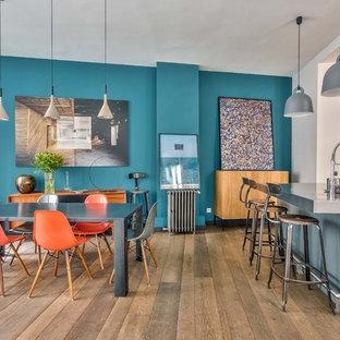 Exemple d'une salle à manger ouverte sur la cuisine chic avec un mur bleu, un sol en bois brun et un sol marron.