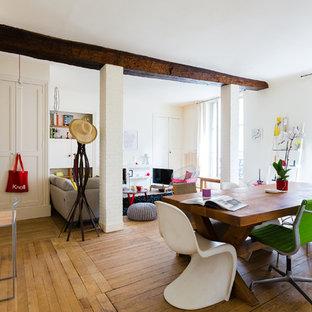Réalisation d'une grande salle à manger ouverte sur le salon design avec un mur blanc et un sol en bois clair.