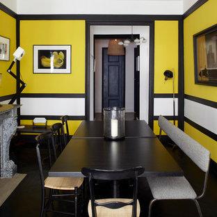 Aménagement d'une salle à manger contemporaine fermée avec un mur multicolore, un sol en bois foncé et une cheminée standard.