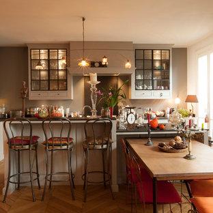 Ejemplo de comedor de cocina bohemio, grande, con paredes grises, chimenea de esquina, marco de chimenea de madera y suelo de madera clara