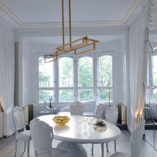 Aménagement d'une grand salle à manger contemporaine fermée avec un mur blanc et un sol en bois brun.