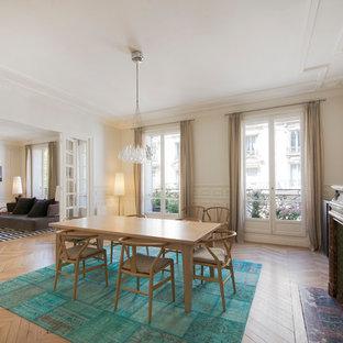 Cette image montre une grande salle à manger ouverte sur le salon traditionnelle avec un mur blanc, une cheminée standard, un sol marron, un sol en bois clair et un manteau de cheminée en pierre.