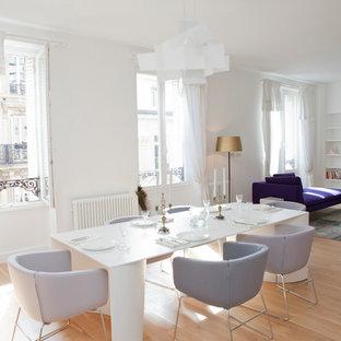 Cette photo montre une grande salle à manger ouverte sur le salon tendance avec un mur blanc, un sol en bois clair, une cheminée standard, un manteau de cheminée en pierre et un sol marron.