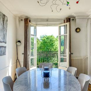 Cette image montre une salle à manger bohème fermée et de taille moyenne avec un mur blanc, un sol en bois clair et aucune cheminée.