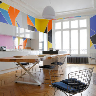 Design ideas for a mid-sized contemporary open plan dining in Paris with multi-coloured walls and medium hardwood floors.