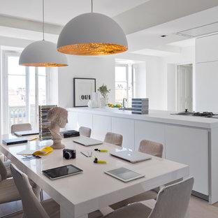 Exemple d'une salle à manger ouverte sur la cuisine tendance de taille moyenne avec un mur blanc, un sol en bois clair, une cheminée standard et un manteau de cheminée en pierre.