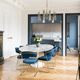 Aménagement d'une salle à manger ouverte sur la cuisine contemporaine avec un mur blanc, un sol en bois clair, un poêle à bois et un sol beige.
