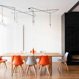 Exemple d'une grand salle à manger ouverte sur le salon tendance avec un mur blanc, un sol en bois brun, une cheminée standard, un manteau de cheminée en carrelage et un sol beige.