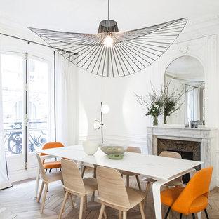 Idées déco pour une salle à manger scandinave avec un mur blanc, un sol en bois clair et une cheminée standard.