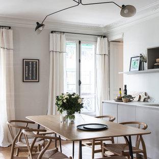 Inspiration pour une salle à manger nordique avec un mur blanc, un sol en bois brun, aucune cheminée et un sol marron.