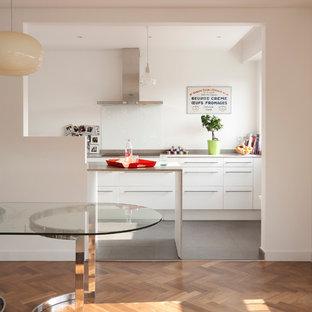 Inspiration pour une salle à manger ouverte sur la cuisine design avec un mur blanc et un sol en bois brun.