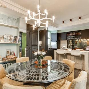 Aménagement d'une salle à manger ouverte sur la cuisine éclectique de taille moyenne avec béton au sol, un mur vert et aucune cheminée.