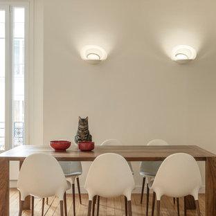 Cette image montre une grande salle à manger ouverte sur le salon design avec un mur blanc, un sol en bois clair, aucune cheminée et un sol marron.