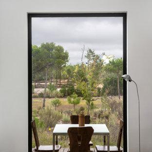 Idée de décoration pour une salle à manger design de taille moyenne avec un mur blanc et un sol gris.