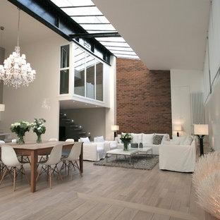 Cette photo montre une grande salle à manger ouverte sur le salon tendance avec un mur multicolore, un sol en bois clair et aucune cheminée.