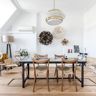 Idée de décoration pour une salle à manger nordique avec un mur blanc, un sol en bois clair, aucune cheminée et un sol beige.