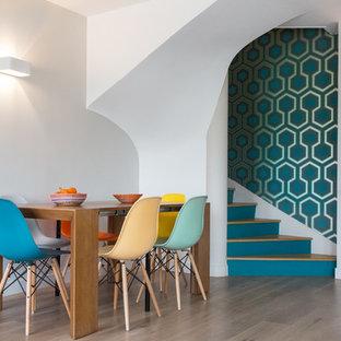 Cette photo montre une salle à manger ouverte sur le salon rétro de taille moyenne avec un mur blanc et un sol en bois clair.