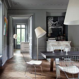 Réalisation d'une grande salle à manger design fermée avec un mur gris, un sol en bois brun, une cheminée standard et un manteau de cheminée en pierre.