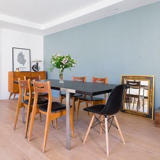 Réalisation d'une salle à manger design fermée avec un mur bleu, un sol en bois clair et aucune cheminée.