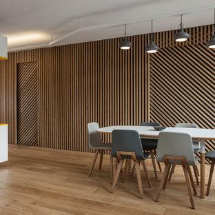 Idée de décoration pour une salle à manger ouverte sur le salon design de taille moyenne avec un sol en bois clair, un mur marron et aucune cheminée.