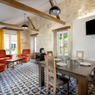 Inspiration pour une salle à manger ouverte sur le salon rustique avec un mur blanc, un sol multicolore et un plafond voûté.