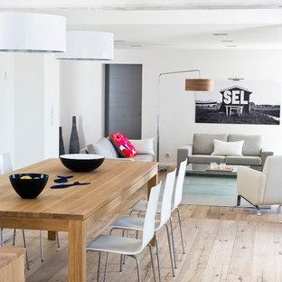 Cette image montre une grand salle à manger ouverte sur le salon marine avec un mur blanc, un sol en bois clair et aucune cheminée.