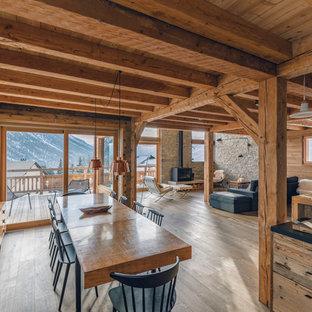 Aménagement d'une grande salle à manger ouverte sur le salon montagne avec un mur blanc et un sol en bois clair.
