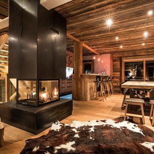 Ispirazione per una grande sala da pranzo aperta verso il soggiorno rustica con pavimento in legno massello medio, camino bifacciale e cornice del camino in metallo