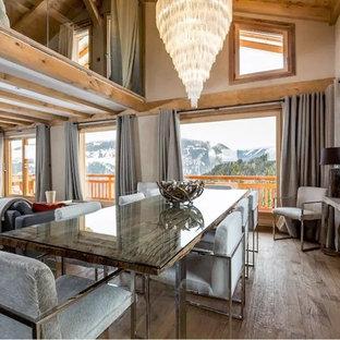 Inspiration pour une salle à manger ouverte sur le salon chalet de taille moyenne avec un mur beige, un sol en bois clair et aucune cheminée.