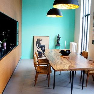 Réalisation d'une salle à manger ouverte sur la cuisine design de taille moyenne avec un mur bleu, béton au sol et aucune cheminée.